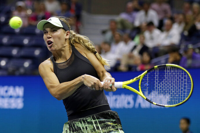 FILE - In this Thursday, Aug. 29, 2019 file photo, Caroline Wozniacki, of Denmark, returns a shot to Danielle Collins during the second round of the U.S. Open tennis tournament, in New York. Wozniacki has announced on Friday, Dec. 6, 2019 she will retire after the Australian Open. (AP Photo/Adam Hunger, file)