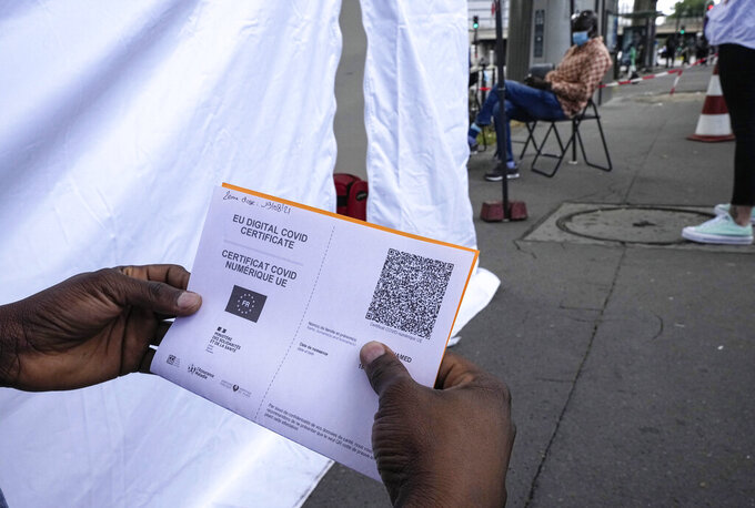 A man holds a virus pass as he waits to be vaccinated at a tent site set up by Doctors Without Borders to vaccinate migrants, the homeless and other marginalized populations in Paris, Thursday, July 29, 2021. Vaccination rates are picking up again in France as the government requires a virus pass for more and more activities, but social workers worry that the measure will further marginalize migrants and other poor populations. (AP Photo/Michel Euler)