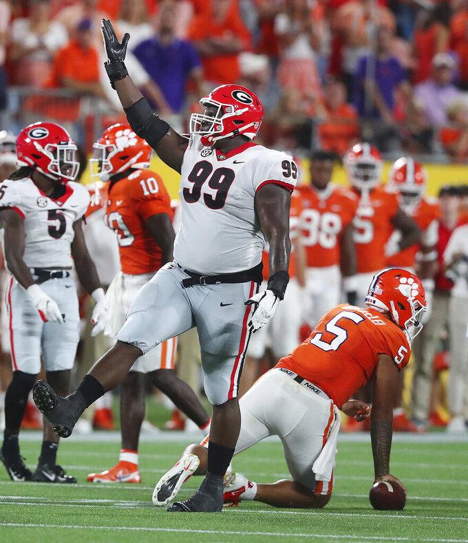 Georgia defensive lineman Jordan Davis celebrates after sacking Clemson quarterback D.J. Uiagalelei, right, during the third quarter of an NCAA college football game Saturday, Sept. 4, 2021, in Charlotte, N.C. (Curtis Compton/Atlanta Journal-Constitution via AP)