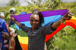 In this photo taken Friday, May 17, 2019, Ali Djabiri, an LGBT refugee from Congo, stands with a rainbow flag at a protest against their treatment by authorities, outside an office of the UN refugee agency UNHCR in Nairobi, Kenya. Kenya's High Court is due to rule Friday, May 24, 2019 on whether laws that criminalize same sex relations are unconstitutional. (AP Photo/Ben Curtis)