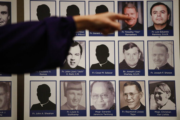 An advocate and survivor of sexual abuse, points to the photos of Catholic priests accused of sexual misconduct by victims during a news conference Thursday, Dec. 6, 2018, in Orange, Calif. Lawyer Mike Reck on Thursday said that's many more than those reported by the Diocese and demanded greater transparency. The Diocese of Orange says the lawyers are trying to re-litigate old claims that the church takes any accusations of abuse