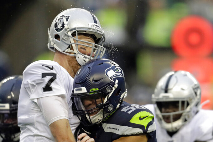 Rain water flies as Oakland Raiders quarterback Mike Glennon, left, is hit by Seattle Seahawks outside linebacker Austin Calitro, right, after catching a pass off during the first half of an NFL football preseason game Thursday, Aug. 29, 2019, in Seattle. (AP Photo/Stephen Brashear)