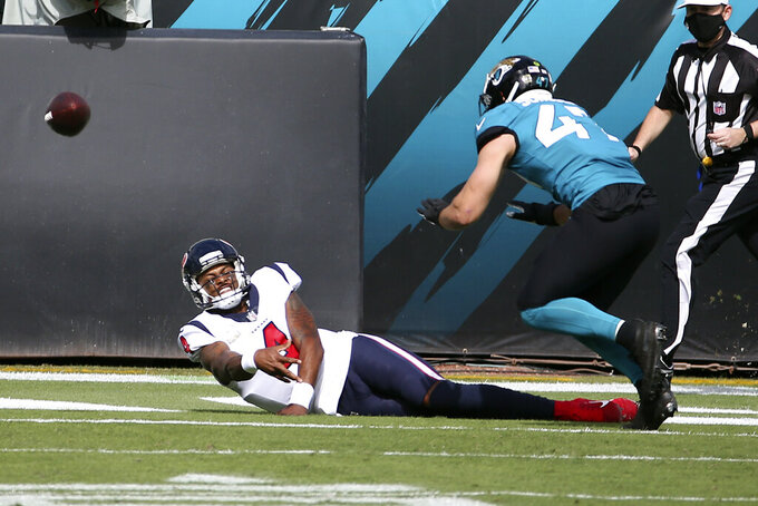 Houston Texans quarterback Deshaun Watson (4) throws a pass as he fall in front of Jacksonville Jaguars linebacker Joe Schobert during the first half of an NFL football game, Sunday, Nov. 8, 2020, in Jacksonville, Fla. (AP Photo/Stephen B. Morton)
