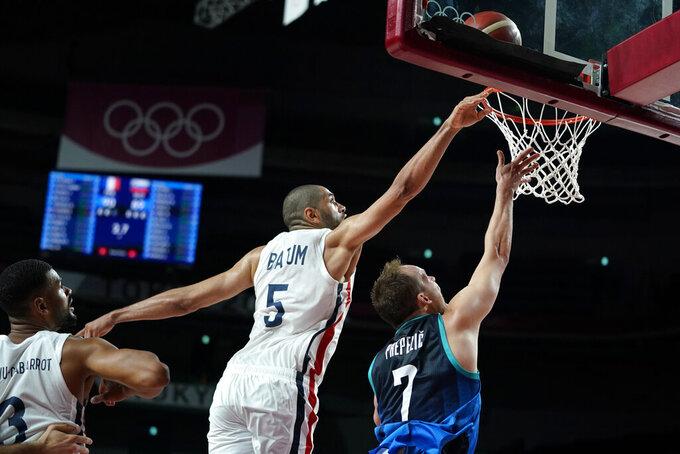 France's Nicolas Batum (5) blocks a shot by Slovenia's Klemen Prepelic (7) during a men's basketball semifinal round game at the 2020 Summer Olympics, Thursday, Aug. 5, 2021, in Saitama, Japan. (AP Photo/Charlie Neibergall)