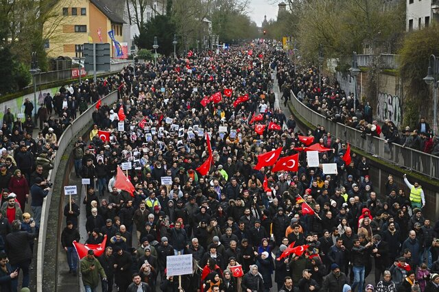 Thousands of people take part in a funeral march in Hanau, Germany, Sunday, Feb. 23, 2020. Several people were killed in a shooting in the central German city late Wednesday, Feb. 19, 2020. (Nicolas Armer/dpa via AP)