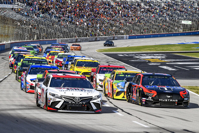 Erik Jones (20) and Clint Bowyer (14) lead the field into turn one during a NASCAR auto race at Texas Motor Speedway, Sunday, Nov. 3, 2019, in Fort Worth, Texas. (AP Photo/Larry Papke)