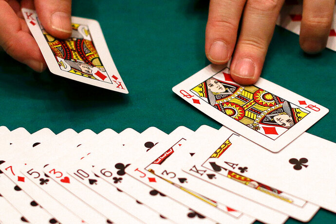 FILE - In this Wednesday, Feb. 27, 2013 file photo, a dealer resets a deck of cards at a casino in Las Vegas. A Cornell University study released on Wednesday, July 17, 2019, created a card game that literally stacked the deck in favor of winners. Yet 60% of those winners thought it was fair, even though they were shown how the deck was stacked. Sociologists say the study tells us about privilege and how we perceive fairness. (AP Photo/Julie Jacobson)