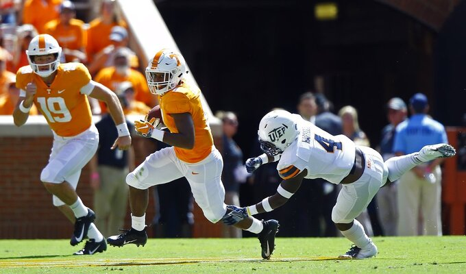 Tennessee running back Ty Chandler (8) runs away from UTEP defensive back Broderick Harrell (4) as quarterback Keller Chryst (19) trails during the first half of an NCAA college football game Saturday, Sept. 15, 2018, in Knoxville, Tenn. (AP Photo/Wade Payne)