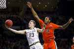 Notre Dame's Dane Goodwin (23) goes in for a layup over Miami's Keith Stone (4) during the second half of an NCAA college basketball game Sunday, Feb. 23, 2020, in South Bend, Ind. (AP Photo/Robert Franklin)