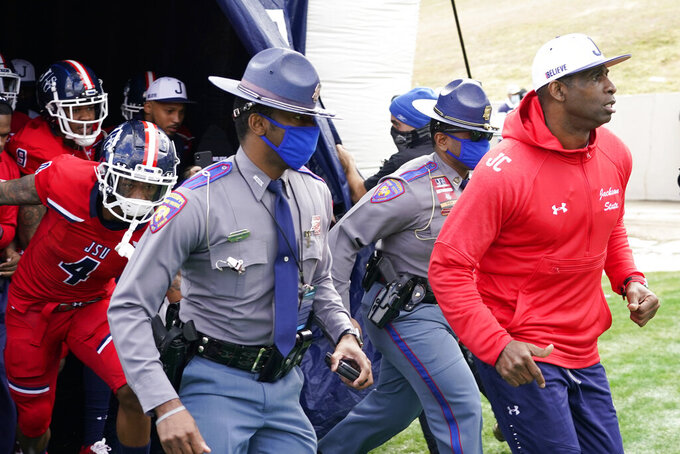 Jackson State football coach Deion Sanders, right, leads an accompanying security detail and his team onto the field prior to the first half of an NCAA college football game against Edward Waters in Jackson, Miss., Sunday, Feb. 21, 2021. The game marks Sanders's collegiate head coaching debut. (AP Photo/Rogelio V. Solis)