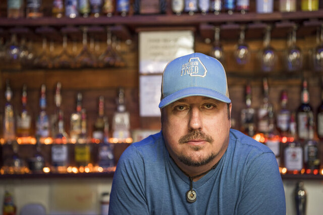 Todd Scott poses behind a bar in Porterdale, Ga.. on June 1, 2016.  Americans' views are starkly different, underscoring the ever-widening divide over gun rights. Last week's arrest of a 17-year-old accused of killing two people during protests in Kenosha, Wisconsin, with a semiautomatic rifle he openly carried is just the latest flashpoint.