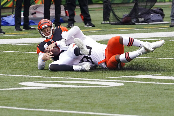 Cincinnati Bengals quarterback Joe Burrow, left, is sacked by Cleveland Browns' Myles Garrett (95) during the first half of an NFL football game, Sunday, Oct. 25, 2020, in Cincinnati. (AP Photo/Bryan Woolston)