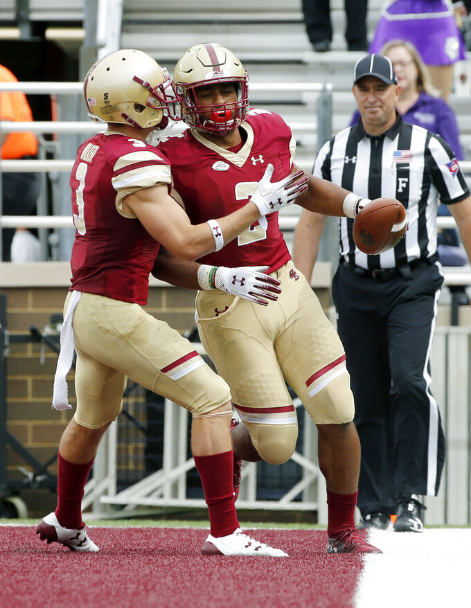 Boston College running back AJ Dillon (2) is congratulated by teammate Michael Walker (3) after scoring a touchdown during the first half of an NCAA college football game against Holy Cross, Saturday, Sept. 8, 2018, in Boston. (AP Photo/Mary Schwalm)
