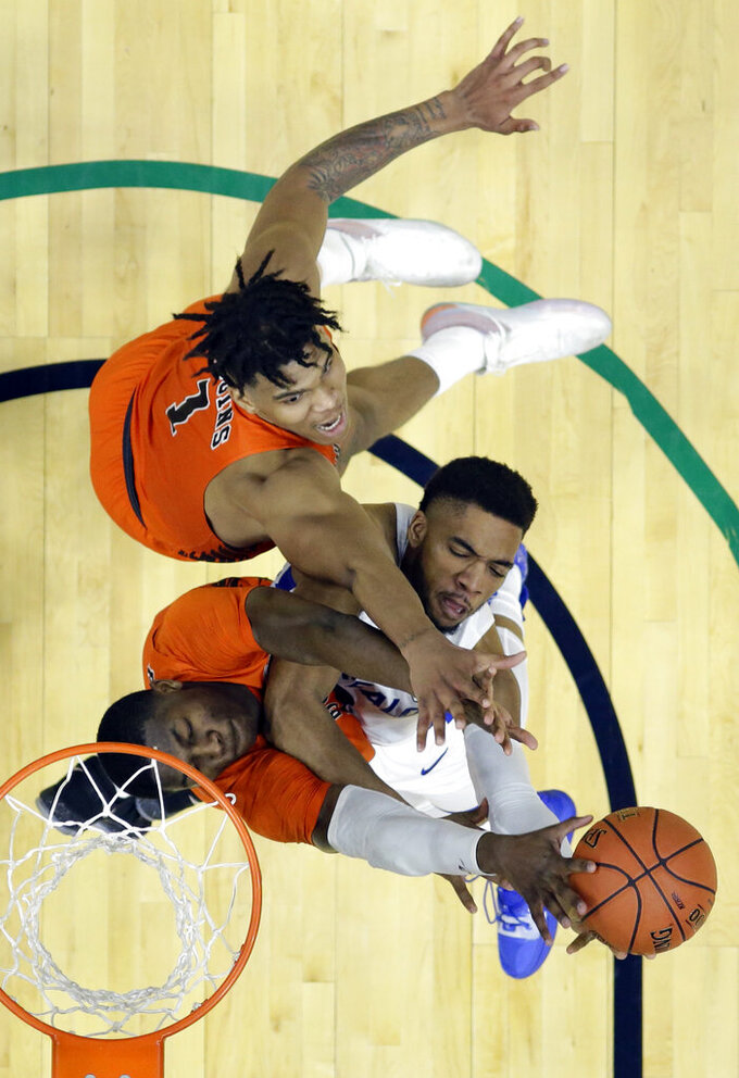 Buffalo's Jayvon Graves, right, drives to the basket against Bowling Green's Daeqwon Plowden, left, and Demajeo Wiggins during the second half of an NCAA college basketball game for the Mid-American Conference men's tournament title Saturday, March 16, 2019, in Cleveland. Buffalo won 87-73. (AP Photo/Tony Dejak)