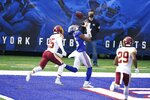 New York Giants' Darius Slayton catches a pass for a touchdown in front of Washington Football Team's Fabian Moreau (25) and Kendall Fuller (29) during the first half of an NFL football game Sunday, Oct. 18, 2020, in East Rutherford, N.J. (AP Photo/John Minchillo)