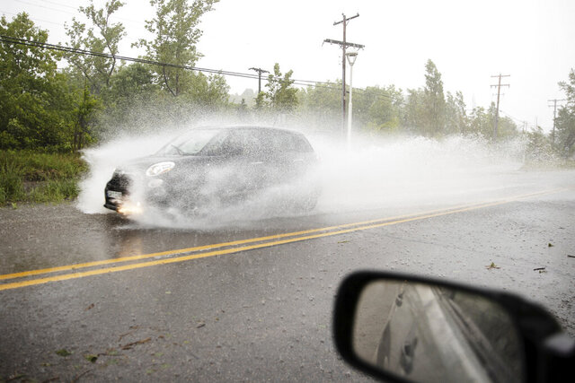 A car drives through water over Ottawa Beach Road in Holland on Wednesday, June 10, 2020. A severe storm blew through the area downing trees and power lines. (Neil Blake/The Grand Rapids Press via AP)