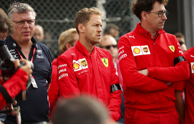 Ferrari driver Sebastian Vettel of Germany, center, and Ferrari team principal Mattia Binotto, right, stand during a moment of silence for Formula 2 driver Anthoine Hubert at the Belgian Formula One Grand Prix circuit in Spa-Francorchamps, Belgium, Sunday, Sept. 1, 2019. The 22-year-old Hubert died following an estimated 160 mph (257 kph) collision on Lap 2 at the high-speed Spa-Francorchamps track, which earlier Saturday saw qualifying for Sunday's Formula One race. (AP Photo/Francisco Seco)