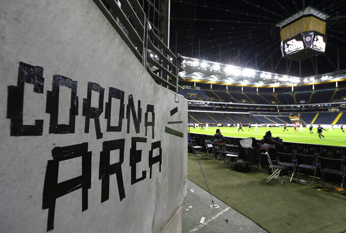 FILE - In this Thursday, March 12, 2020 file photo shows a sign taped by Eintracht fans on a wall of the stadium during a Europa League round of 16, 1st leg soccer match between Eintracht Frankfurt and FC Basel in Frankfurt, Germany. German Bundesliga will restart on May 16. (AP Photo/Michael Probst)
