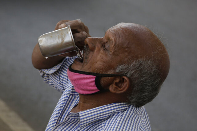 An Indian man selling earthen pots beneath a bridge drinks water in Ahmedabad, India, Thursday, May 28, 2020. India faced scorching temperatures and the worst locust invasion in decades on Thursday as authorities prepared for the end of a months-long coronavirus lockdown despite recording thousands of new infections every day. (AP Photo/Ajit Solanki)