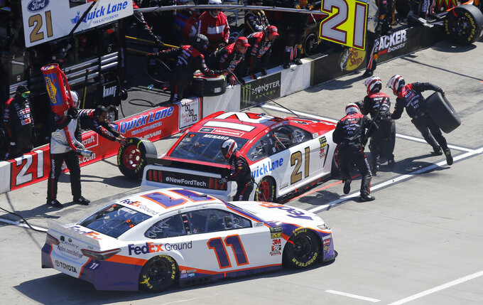 Denny Hamlin (11) dries out of his pit stall past Paul Menard (21) during a NASCAR Cup Series auto race at Martinsville Speedway in Martinsville, Va., Sunday, March 24, 2019. (AP Photo/Steve Helber)