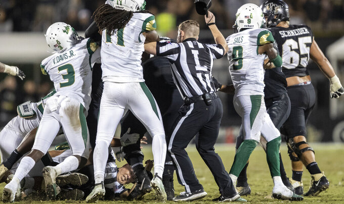 The face of official Bill Lamkin is seen at the bottom of a pile of fighting Central Florida and South Florida players during the first half of an NCAA college football game Friday, Nov. 29, 2019, in Orlando, Fla. (AP Photo/Willie J. Allen Jr.)