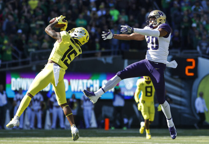 Oregon cornerback Deommodore Lenoir (15), intercepts a pass intended for Washington wide receiver Ty Jones (20), on Washington's first drive during a NCAA college football game in Eugene, Ore., Saturday, Oct. 13, 2018. The play set up an Oregon field goal. (AP Photo/Thomas Boyd)