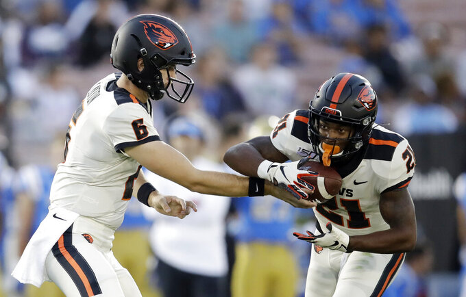 Oregon State running back Artavis Pierce, right, gets a hand-off from quarterback Jake Luton during the first half of an NCAA college football game against UCLA, Saturday, Oct. 5, 2019, in Pasadena, Calif. (AP Photo/Marcio Jose Sanchez)