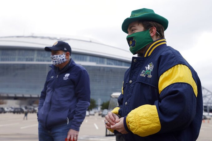 Notre Dame fan Andrew Bub, right, of Dallas, plays games with others as they tailgate outside AT&T Stadium before the Rose Bowl NCAA college football game against Alabama in Arlington, Texas, Friday, Jan. 1, 2021. (AP Photo/Michael Ainsworth)