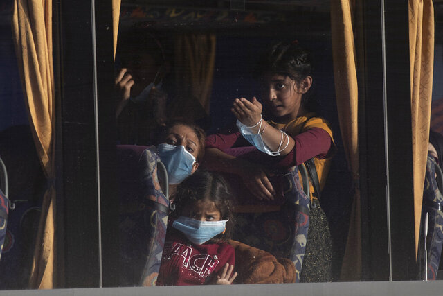 Refugees and migrants wearing protective masks to help curb the spread of coronavirus leave on a bus after their arrival at the port of Lavrio, about 75 kilometers (48miles) south of Athens, on Tuesday, Sept. 29, 2020. Greek authorities have moved nearly 1,000 asylum-seekers from eastern Aegean islands to the mainland as part of efforts to improve conditions in overcrowded island camps. Most of the people on a ferry that docked Tuesday at Lavrio, near Athens, were from a temporary facility hastily built on the island of Lesbos to replace a squalid camp that angry residents burned down three weeks ago. (AP Photo/Petros Giannakouris)