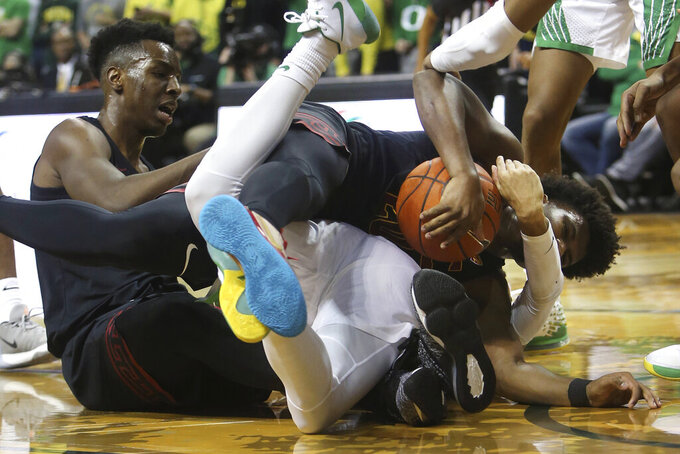Southern California's Onyeka Okongwu, left, and Ethan Anderson, right, battle Oregon's Anthony Mathis, center, for a loose ball during the first half of an NCAA basketball game in Eugene, Ore., Thursday, Jan. 23, 2020. (AP Photo/Chris Pietsch)