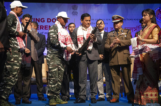 Assam Chief minister Sarbananda Sonowal, third from right, receives arms from one of the rebels who surrendered during a ceremony in Gauhati, India, Thursday, Jan. 23, 2020. More than 600 insurgents belonging to eight different rebel groups have surrendered to Indian authorities in this troubled northeastern state, responding to the government's peace initiative to rejoin mainstream society. (AP Photo/Anupam Nath)