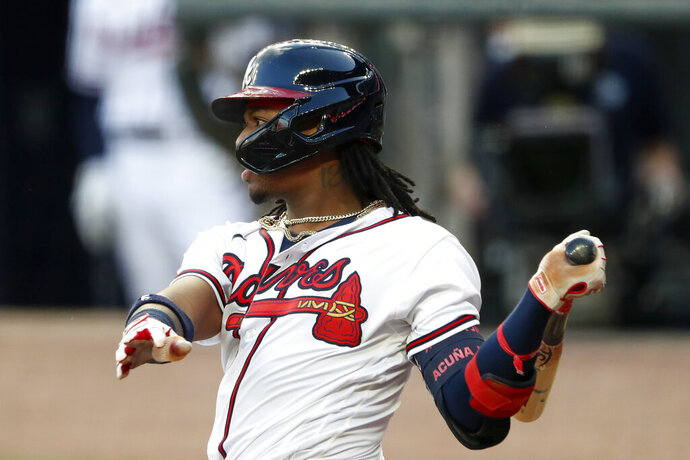 Atlanta Braves' Ronald Acuña Jr. follows through on an RBI double during the second inning of the team's baseball game against the New York Mets on Saturday, Aug. 1, 2020, in Atlanta. (AP Photo/John Bazemore)
