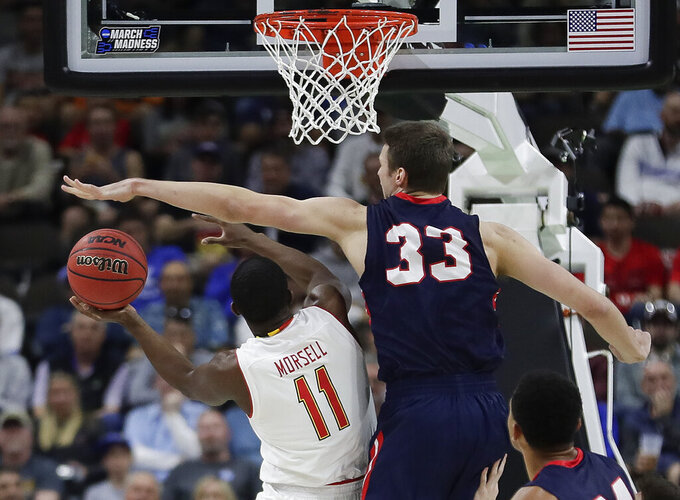 Maryland 's Darryl Morsell (11) attempts a shot as Belmont 's Nick Muszynski (33) defends during the first half of a first round men's college basketball game in the NCAA Tournament, in Jacksonville, Fla. Thursday, March 21, 2019. (AP Photo/John Raoux)