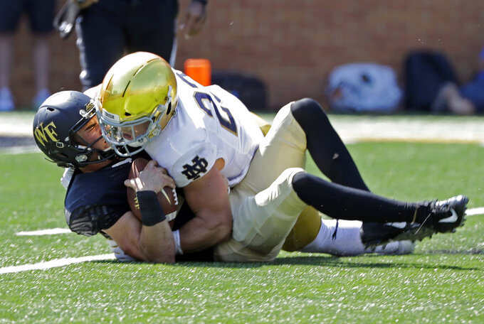 FILE - In this Sept. 22, 2018, file photo, Wake Forest's Sam Hartman (10) is sacked by Notre Dame's Drue Tranquill (23) in the first half of an NCAA college football game in Winston-Salem, N.C. No. 2 Clemson plays No. 3 Notre Dame in the Cotton Bowl on Dec. 29, 2018. (AP Photo/Chuck Burton, File)