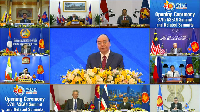 A screen shows ASEAN leaders attending an online summit, in Hanoi, Vietnam Thursday, Nov. 12, 2020. Clockwise from top left: Brunei Sultan Hassanal Bolkiah, Cambodian Deputy Prime Minister Aun Pornmoniroth, Indonesian President Joko Widodo, Malaysia Prime Minister Muhyiddin Yassin, Philippine President Rodrigo Duterte, ASEAN Secretary General Lim Jock Hoi, Thai President Prayuth Chan-ocha, Singaporean President Lee Hsien Loong, Myanmar State Counsellor Aung San Suu Kyi, Laos Prime Minister Thongloun Sisoulith and Vietnam's Prime Minister Nguyen Xuan Phuc is at center. (VNA via AP)