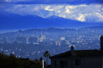 Heavy storm clouds and snow are seen in the San Gabriel mountain range behind an area of downtown Los Angeles on Friday, Nov. 29, 2019. California is drenched or blanketed in snow after a powerful Thanksgiving storm. Rain and snow showers are continuing in parts of the state Friday morning while skies are clearing elsewhere.(AP Photo/Richard Vogel)