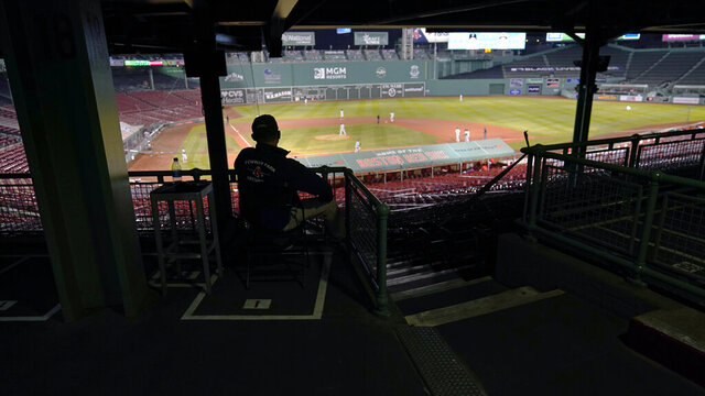 A Boston Red Sox security guard watches from stands empty of fans during the fifth inning of a baseball game between the Red Sox and the Baltimore Orioles at Fenway Park in Boston, Thursday, Sept. 24, 2020. The Red Sox played their final home game of the COVID-19-disrupted season. (AP Photo/Charles Krupa)