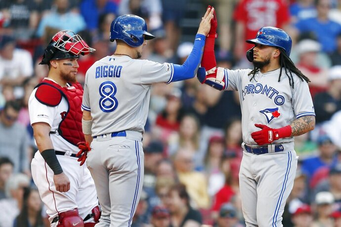 Toronto Blue Jays' Freddy Galvis, right, celebrates his two-run home run that drove in Cavan Biggio (8) as Boston Red Sox's Christian Vazquez stands near the plate during the seventh inning of a baseball game in Boston, Saturday, June 22, 2019. (AP Photo/Michael Dwyer)