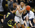 Colorado guard Tyler Bey, right, looks to pass the ball as Oregon forward Francis Okoro, back left, and guard Will Richardson defend in the first half of an NCAA basketball game Saturday, Feb. 2, 2019, in Boulder, Colo. (AP Photo/David Zalubowski)