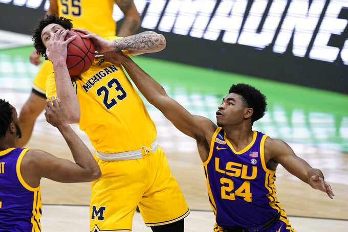 Michigan forward Brandon Johns Jr. (23) grabs a rebound over LSU guard Cameron Thomas (24) during the first half of a second-round game in the NCAA men's college basketball tournament at Lucas Oil Stadium Monday, March 22, 2021, in Indianapolis. (AP Photo/Darron Cummings)