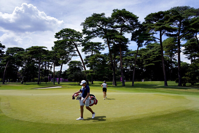 Albane Valenzuela, of Switzerland, and her brother and caddy, Alexis Valenzuela, practice on the 11th green during a practice round prior to the women's golf event at the 2020 Summer Olympics, Monday, Aug. 2, 2021, at the Kasumigaseki Country Club in Kawagoe, Japan. (AP Photo/Matt York)