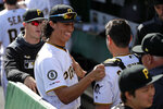 Pittsburgh Pirates' shortstop Cole Tuckert, center, walks through the dugout before taking the field for his first major league baseball game against the San Francisco Giants in Pittsburgh, Saturday, April 20, 2019. (AP Photo/Gene J. Puskar)