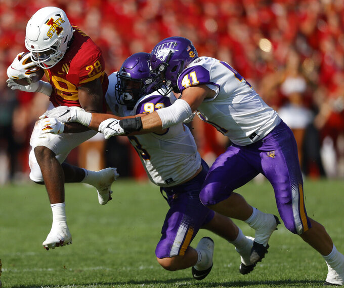 Iowa State running back Breece Hall (28) leaps as he runs the ball as he is tackled by Northern Iowa defensive lineman Caden Houghtelling (93) and linebacker Spencer Cuvelier (41) during the first half of an NCAA college football game, Saturday, Sept. 4, 2021, in Ames, Iowa. (AP Photo/Matthew Putney)