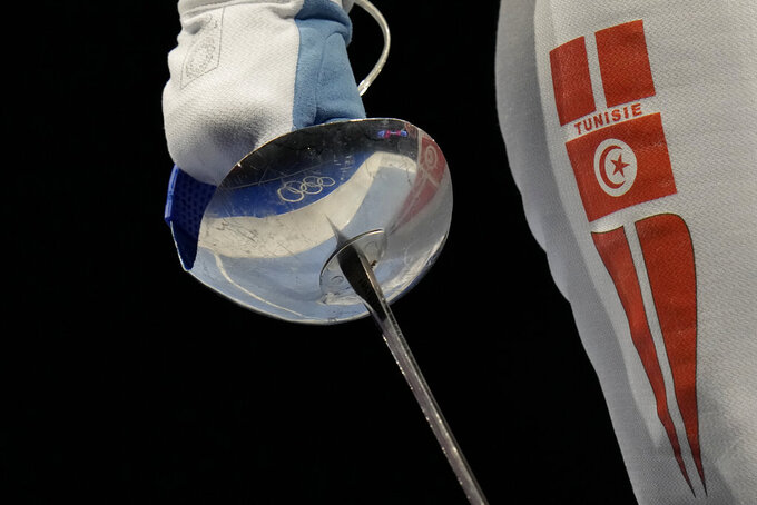 The Olympic rings are reflected on Sabre weapon of Olfa Hezami of Tunisia as competes with Norika Tamura of Japan in the women's Sabre team round of 16 competition at the 2020 Summer Olympics, Saturday, July 31, 2021, in Chiba, Japan. (AP Photo/Hassan Ammar)