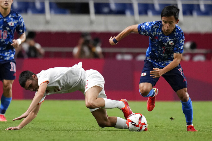 Spain's Pedri Gonzalez, left, and Japan's Takefusa Kubo battle for the ball in a men's semifinal soccer match at the 2020 Summer Olympics, Tuesday, Aug. 3, 2021, in Saitama, Japon. (AP Photo/Silvia Izquierdo)