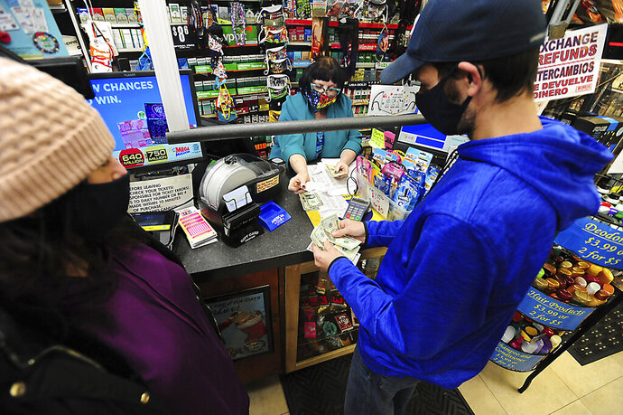 Michael and Amanda Lazovich of Plain, Pa., purchase Powerball and Mega Millions lottery tickets at the Anthracite Newsstand on Public Square in Wilkes-Barre, Pa., Thursday, Jan. 14, 2021. The next Mega Millions drawing is Friday night, when an estimated $750 million prize will be up for grabs. The drawing for an estimated $640 million Powerball jackpot will be Saturday night. (Mark Moran/The Citizens' Voice via AP)
