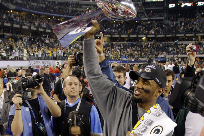 FILE - In this Feb. 6, 2011, file photo, Green Bay Packers' Charles Woodson holds up the Vince Lombardi Trophy while celebrating the Packers' 31-25 win against the Pittsburgh Steelers in NFL football's Super Bowl XLV in Arlington, Texas. Woodson, in his first-year of eligibility, was selected as a finalist for the Pro Football Hall of Fame's class of 2021 on Tuesday, Jan. 5, 2021. (AP Photo/Eric Gay, File)