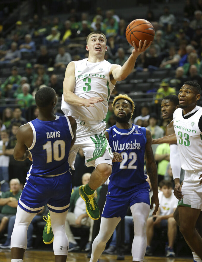 CORRECTS SPELLING OF NAME TO PRITCHARD NOT PRICHARD Oregon's Payton Pritchard goes up for a basket against Texas-Arlington's Radshad Davis, left, Tiandre Jackson-Young with teammate Francis Okoro, right, during the first half of an NCAA college basketball game in Eugene, Ore., Sunday, Nov. 17, 2019. (AP Photo/Chris Pietsch)