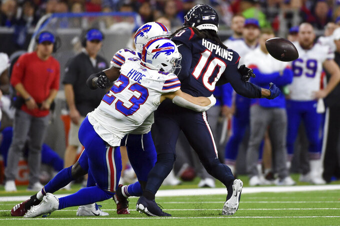 Houston Texans wide receiver DeAndre Hopkins (10) fumbles the ball as he is hit by Buffalo Bills' Micah Hyde (23) and Tre'Davious White during the second half of an NFL wild-card playoff football game Saturday, Jan. 4, 2020, in Houston. The Bills recovered the fumble.(AP Photo/Eric Christian Smith)