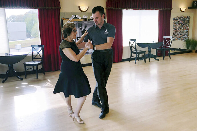 In this Oct. 7, 2019, photo, dance instructor Ned Pavlovic, a native of Serbia, teaches his student Rouhy Yazdani, a native of Iran who now lives in Milford, Conn., some ballroom dance moves at the Fred Astaire Dance studio in Orange, Conn. Owners of Ballroom dance studios including the Fred Astaire studio say the immigration clampdown has made it even more difficult to find qualified instructors. The small business owners, U.S. dance studio chains and immigration attorneys say there's greater backlogs for visa applications and an overall increase in evidence requests, including for redundant and unnecessary documents. (AP Photo/Susan Haigh)